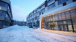 glass entrance of business center and courtyard at winter evening
