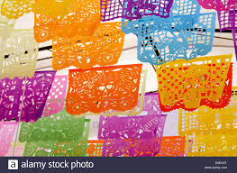 brightly colored cut paper flags with day of the dead designs in