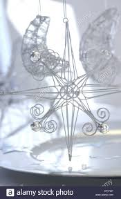 ornate silver star and moon christmas decorations made from wire ornate silver star and moon christmas decorations made from wire and baubles hanging above silver plate