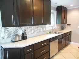 black color scheme kitchen cabinet with white granite counter top