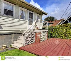 small grey house with staircase to back yard deck stock photos