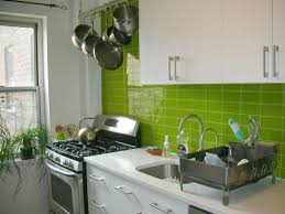 white glossy modern kitchen cabinets in a kitchen with green tile