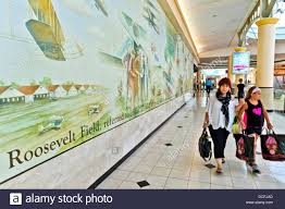 garden city new york usa 15th august 2013 at roosevelt field at roosevelt field shopping mall a mother and daughter carrying shopping bags walks past a wall mural depicting aviation scenes from the site s past