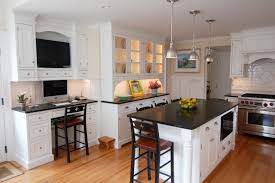 white kitchen island with black granite top white wooden kitchen cabinet with black counter top and glass door