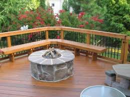 here u0027s a wooden deck with a stone fire pit in the middle a pool