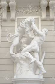 antique statue of a greek male god wrestling a lion stock photo