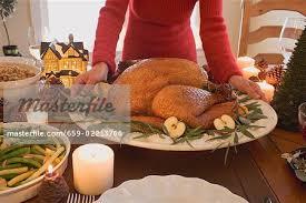 Turkey On The Table Woman Putting Roast Turkey On Christmas Table Usa Stock Photo