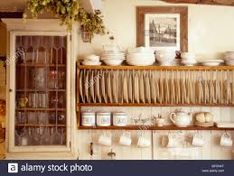 close up of cream bowls on wooden plate rack beside small wall