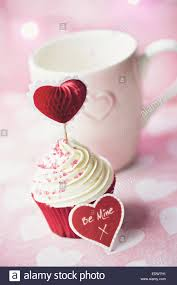 cupcake decorated with a heart shaped cake pick stock photo