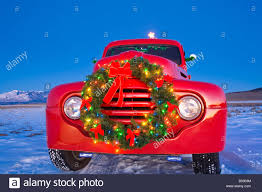 vintage ford pick up truck with christmas wreath and tree in back