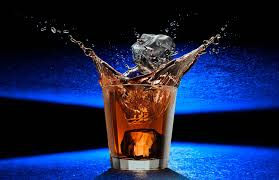 cocktail photography ice drop whiskey splash photograph on a futuristic blue surface by