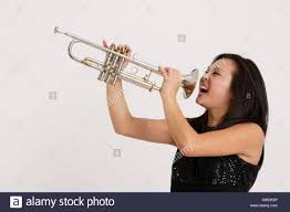 stock photograph of a pretty asian screaming into a trumpet