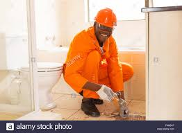 cheerful african american construction worker removing floor tiles