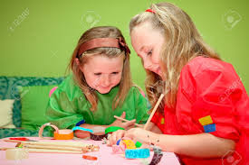 happy smiling children playing drawing and making craft in class