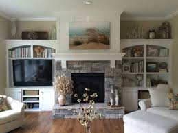 the top of the shelves gas fireplace with stacked stone pieced hearth corbels board and batten detail above the mantle and built ins on both sides