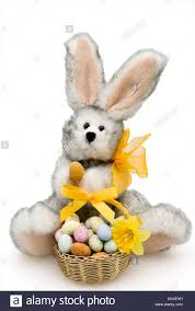 fluffy easter bunny cuddly toy holding a chocolate easter egg with