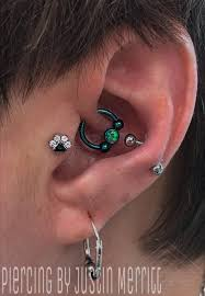 paw print tragus piercing and a daith blue horseshoe tattoo