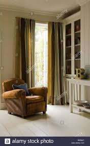Distressed Leather Armchairs Distressed Leather Armchair With Curtains Fabric By Jim Thompson