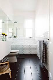 narrow bathroom with black floors and subway tiles decorating