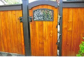 custom arch top cedar fence with ornamental iron features fence