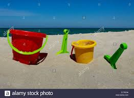 plastic buckets and shovels on sandy beach at baltic sea stock