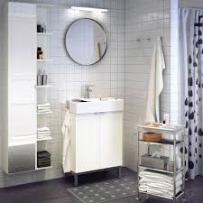 bathroom white tile wall with round wall mirror also wall mount