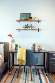 wheeled black small corner desk in bedroom with floating shelves