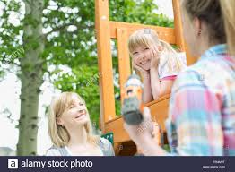 three generations in backyard with play structure stock photo