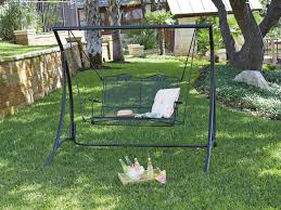 fetching black metal porch swing in c shape on green lawn of metal