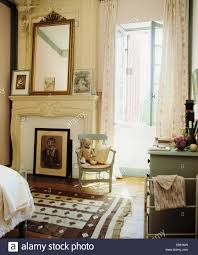 antique mirror above fireplace in cream french country bedroom
