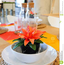 artificial plant with orange flower in plastic pot stock photo