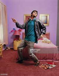 teenage boy dancing in teenage girls pink bedroom stock photo