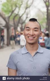 young looking haircut young man with mohawk haircut smiling looking at camera stock