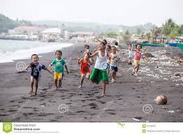 children group on the beach with volcanic sand near mayon volcano