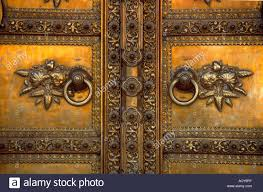 a golden door with floral designs at the entrance to the city