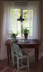 a writing table next to a window looking out onto a garden