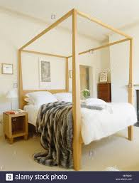 four post bed faux fur throw on modern pale wood four poster bed in cream
