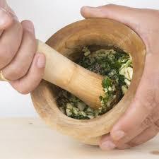 cuisiner l ail chef écraser l ail et le persil avec mortier et un pilon dans le k