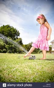 little playing with lawn sprinkler in the garden stock photo