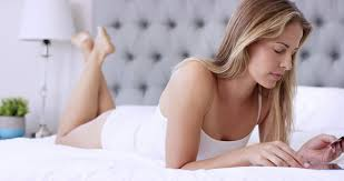 attractive young woman shopping online using digital tablet lying