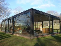 front yard modern glass house design with small garden and white