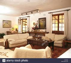 coffee table in spanish cream sofas and dark wood coffee table in living room of spanish