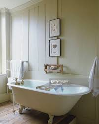 bathroom with white woodpanelled walls framed drawings of sea