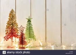 Wooden Toy Christmas Tree Decorations - toy christmas tree and christmas lights on wood background stock