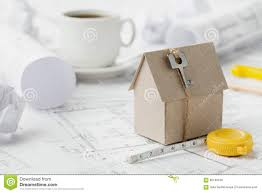 model cardboard house with key and tape measure on blueprint home