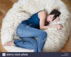woman on furry bean bag chair in living room stock photo royalty