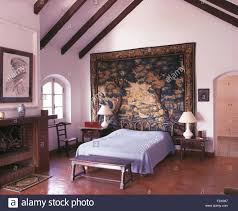 tiled bedroom has large antique tapestry behind bed in white
