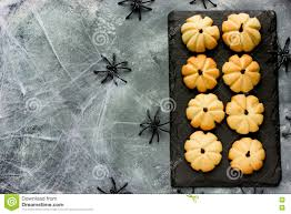 halloween pumpkin cookies for kids on a black slate plate on a g