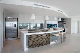 new penthouse kitchen with curved island and wood veneer upstand