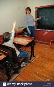desk for 6 year old p32 189 6 year old boy raises hand at desk as mom plays teacher at